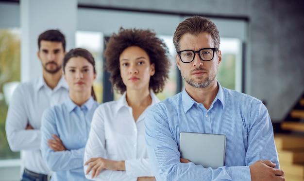 Grupo multicultural de empresários em pé com os braços cruzados em uma fileira. foco seletivo no homem em primeiro plano, que está segurando as mãos de lata de mesa.