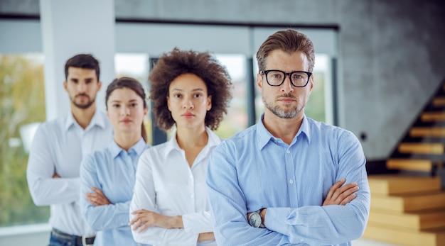 Grupo multicultural de empresários em pé com os braços cruzados em uma fileira. foco seletivo no homem em primeiro plano.