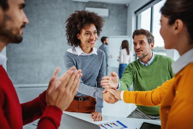 Grupo multicultural de empresários em pé na sala de reuniões e em reuniões. duas mulheres apostam em terminar o projeto a tempo.