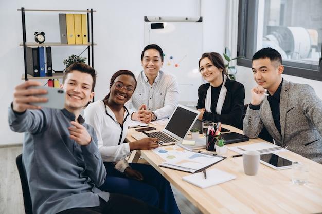 Grupo multicultural de empresários profissionais fazendo selfie no escritório moderno