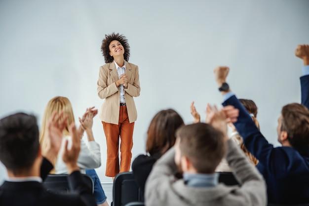 Grupo multicultural de empresários torcendo e batendo palmas para uma mulher de negócios mestiça que acabou de terminar seu discurso.