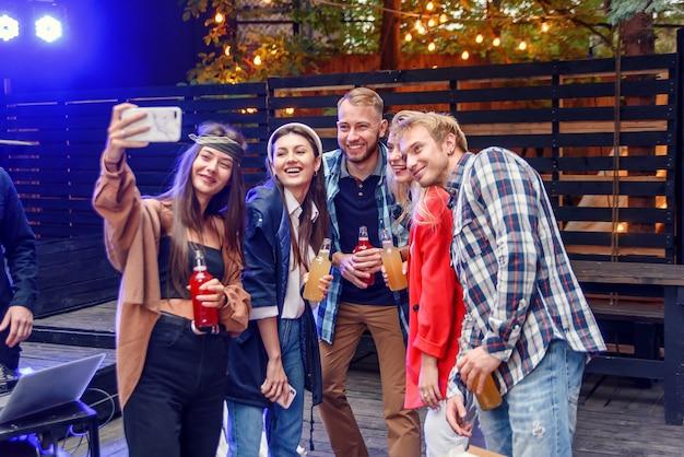 Grupo multiétnico. bonitão barbudo está fazendo selfie com seus amigos na festa em sua câmera do telefone. todos estão sorrindo e curtindo sua companhia, se divertindo