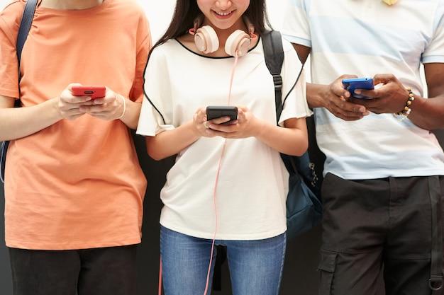 Grupo multiétnico de alunos irreconhecíveis usando um smartphone conectado a pessoas sorridentes