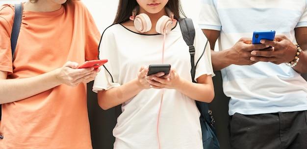 Grupo multiétnico de alunos irreconhecíveis usando um smartphone