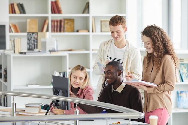Grupo multiétnico de alunos usando equipamentos de telecomunicações enquanto estudam na biblioteca da faculdade e sorrindo,