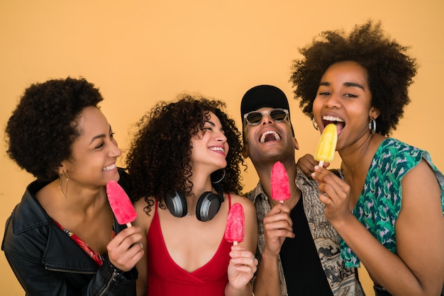 Grupo multiétnico de amigos, aproveitando o verão enquanto come sorvete.