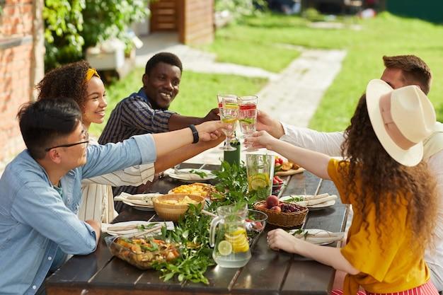 Grupo multiétnico de amigos brindando com copos de coquetel enquanto desfruta de um jantar ao ar livre no verão