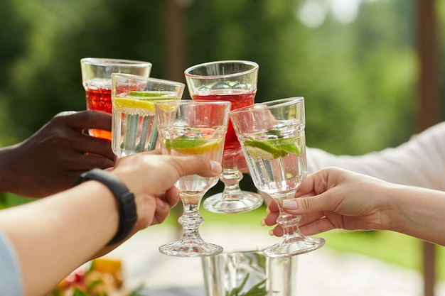 Grupo multiétnico de amigos brindando com copos de coquetel enquanto desfruta de uma festa ao ar livre no verão