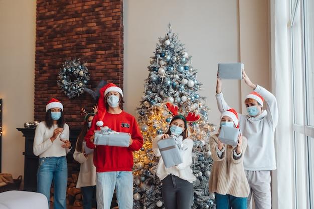 Grupo multiétnico de amigos com chapéus de papai noel, sorrindo e posando com os presentes nas mãos