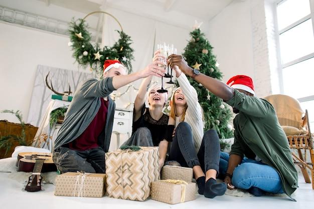 Grupo multiétnico de amigos comemorando e brindando com taças de champanhe
