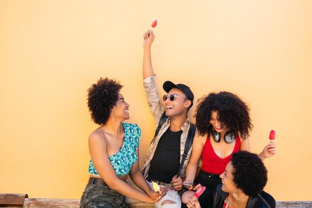 Grupo multiétnico de amigos curtindo o verão enquanto tomam sorvete
