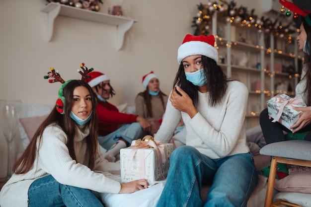 Grupo multiétnico de amigos em chapéus de papai noel, sorrindo e posando para a câmera com os presentes nas mãos. o conceito de celebrar o ano novo e o natal sob restrições do coronavírus. feriado em quarentena