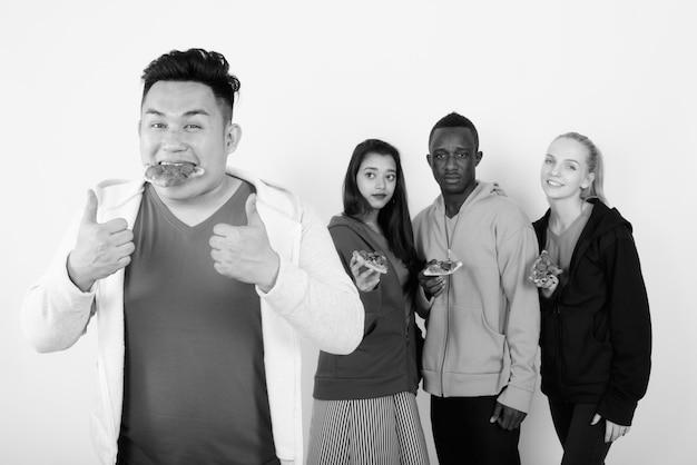 Grupo multiétnico de amigos juntos como conceito de diversidade contra uma parede branca em preto e branco
