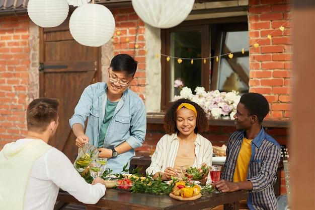 Grupo multiétnico de amigos sentados à mesa de madeira enquanto desfrutam de um jantar ao ar livre na festa de verão
