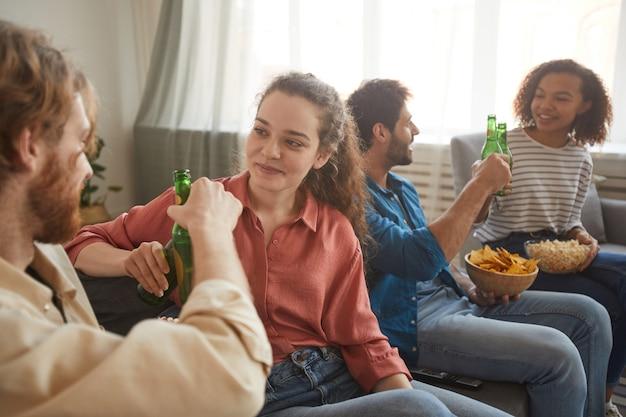 Grupo multiétnico de amigos tocando garrafas de cerveja enquanto assistem tv juntos, sentados no confortável sofá em casa, foco no jovem casal em primeiro plano