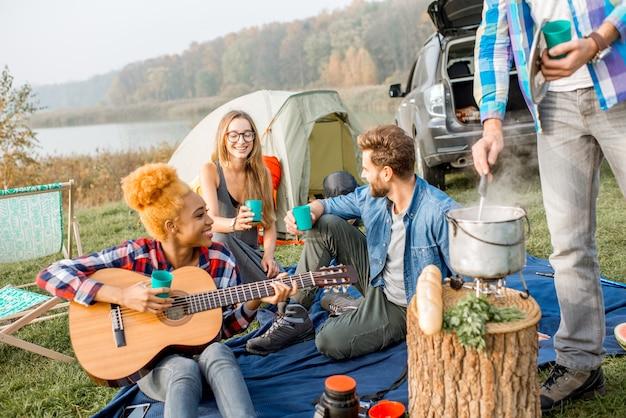 Grupo multiétnico de amigos usando copos que tilintam casualmente durante o jantar ao ar livre no acampamento