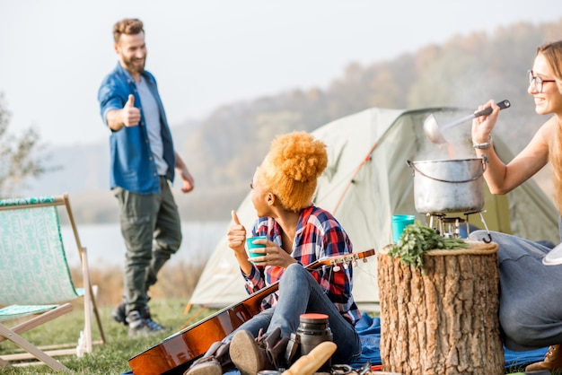 Grupo multiétnico de amigos vestidos casualmente fazendo um piquenique, cozinhando sopa com caldeirão durante a recreação ao ar livre perto do lago