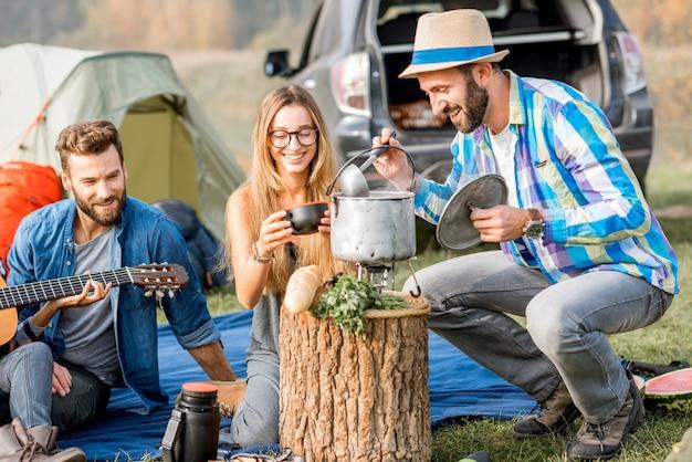 Grupo multiétnico de amigos vestidos de forma casual fazendo um piquenique, cozinhando sopa com caldeirão durante a recreação ao ar livre com barraca, carro e equipamento de caminhada perto do lago