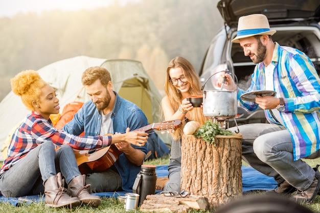 Grupo multiétnico de amigos vestidos de forma casual fazendo um piquenique, cozinhando sopa com o caldeirão, tocando violão durante recreação ao ar livre perto do lago
