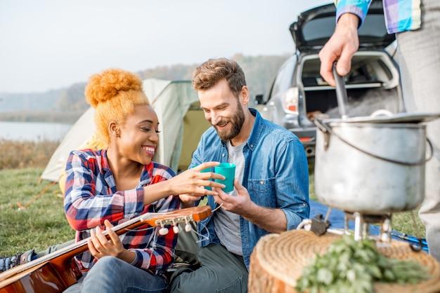 Grupo multiétnico de amigos vestidos de forma casual para um saboroso jantar com sopa cozida no caldeirão durante o piquenique no acampamento