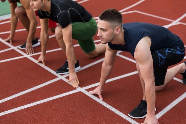 Grupo multiétnico de atletas pronto para correr