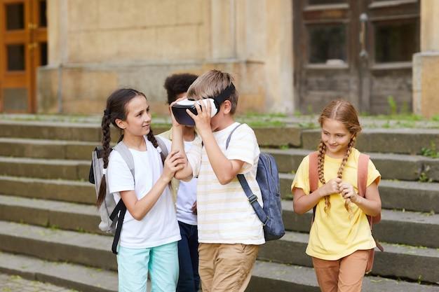 Grupo multiétnico de crianças alegres em idade escolar brincando com óculos de realidade virtual ao ar livre, foco no garoto usando equipamento, copie o espaço