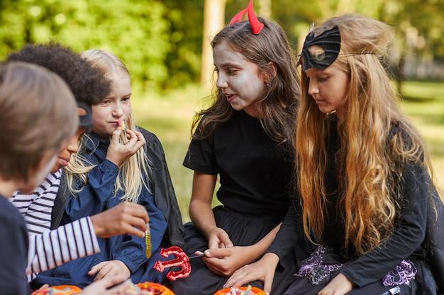 Grupo multiétnico de crianças comendo doces no halloween ao ar livre enquanto usavam fantasias