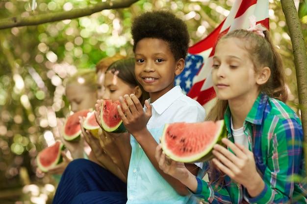 Grupo multiétnico de crianças comendo melancia sentadas em fileira enquanto brincam ao ar livre no verão