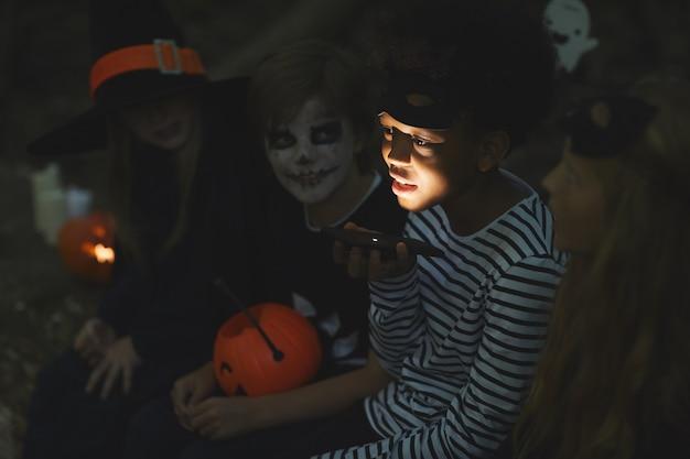 Grupo multiétnico de crianças contando histórias assustadoras no halloween, foco no garoto afro-americano segurando uma lanterna em primeiro plano