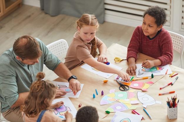 Grupo multiétnico de crianças desenhando com giz de cera enquanto aproveitam as aulas de arte e artesanato na pré-escola ou no centro de desenvolvimento