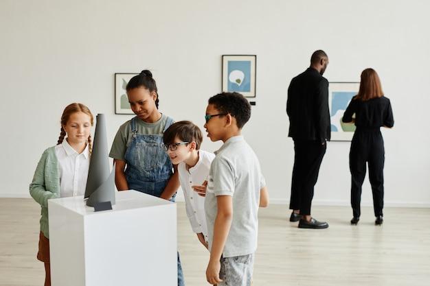 Grupo multiétnico de crianças olhando esculturas na galeria de arte moderna, copie o espaço