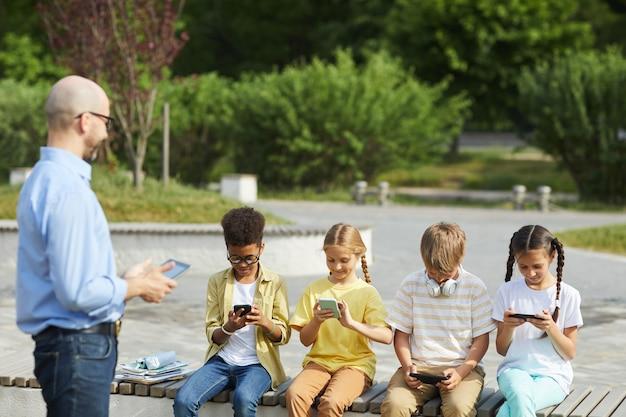 Grupo multiétnico de crianças usando tablets digitais enquanto estão sentadas em um banco durante uma aula ao ar livre com um professor sorridente, copie o espaço