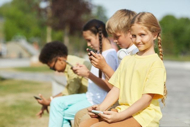 Grupo multiétnico de crianças usando tablets e smartphones enquanto está sentado em uma fileira ao ar livre sob a luz do sol, foco na garota loira sorridente em primeiro plano, copie o espaço