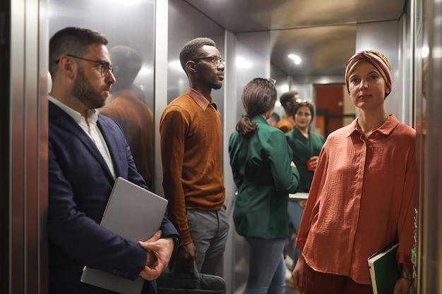 Grupo multiétnico de empresários em pé no elevador com a porta aberta, foco na jovem mulher em primeiro plano, espaço de cópia