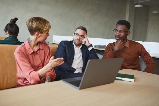 Grupo multiétnico de empresários se comunicando ativamente enquanto discutem o projeto de trabalho no escritório, copie o espaço