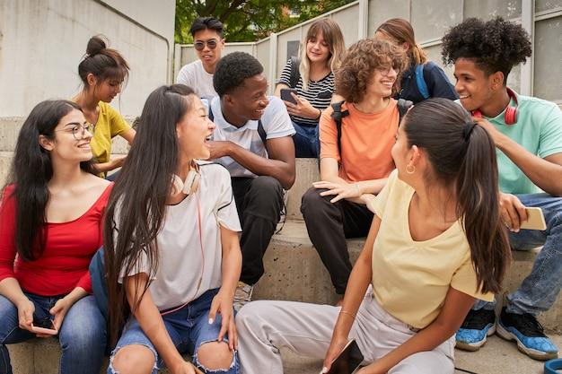 Grupo multiétnico de estudantes felizes em uma pausa, os jovens riem sentados nas escadas do alto ...