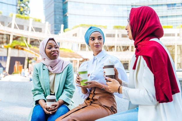 Grupo multiétnico de garotas muçulmanas vestindo roupas casuais e tradicional hijab se divertindo ao ar livre - 3 garotas árabes