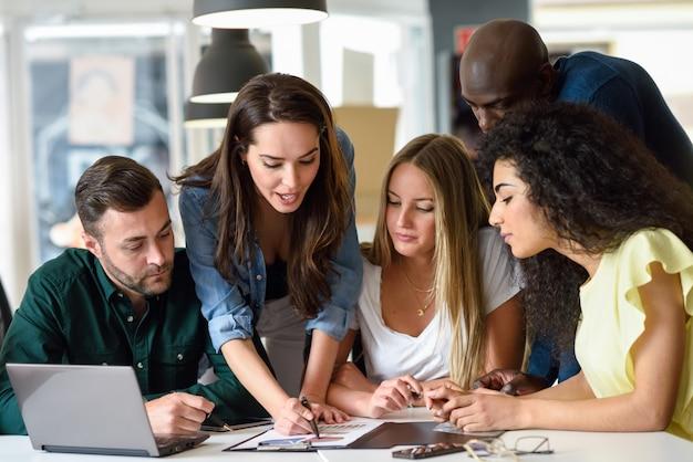 Grupo multiétnico de homens e mulheres jovens que estudam em ambientes fechados.