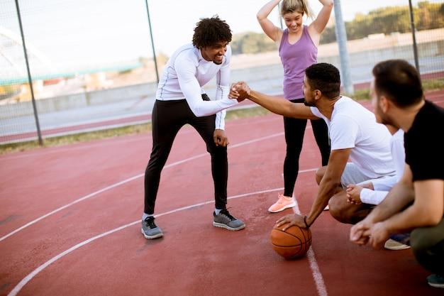 Grupo multiétnico de jogadores de basquete descansando na quadra