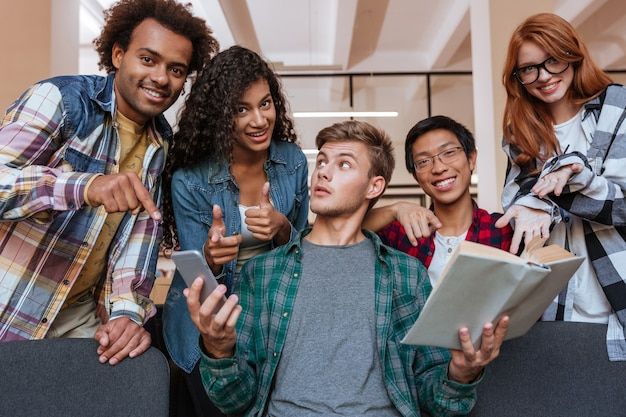 Grupo multiétnico de jovens alegres em pé e apontando para um aluno com um livro e um smartphone