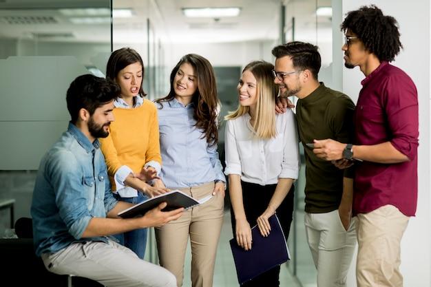 Grupo multiétnico de jovens em pé no escritório moderno e de brainstorming