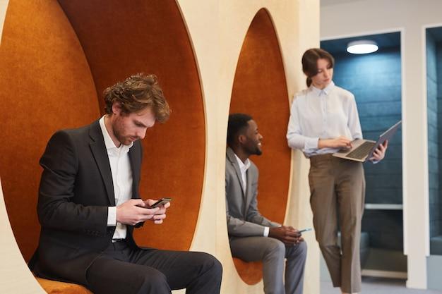 Grupo multiétnico de jovens empresários trabalhando no interior de um escritório contemporâneo ou centro de coworking, foco no homem barbudo usando smartphone em primeiro plano, copie o espaço