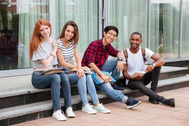 Grupo multiétnico de jovens estudantes alegres sentados em escadas ao ar livre