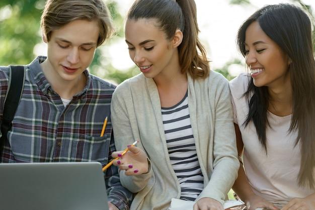 Grupo multiétnico de jovens estudantes sorridentes usando computador portátil