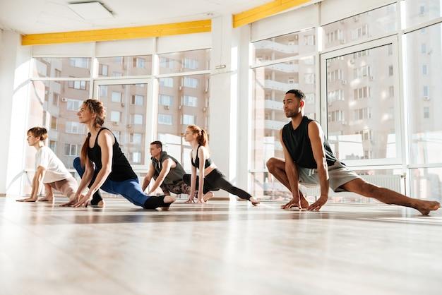 Grupo multiétnico de jovens praticando ioga juntos