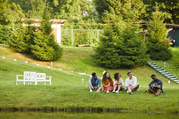 Grupo multiétnico de jovens sentados perto da água e ouvindo um afro-americano tocando violão enquanto aproveitam as férias de verão
