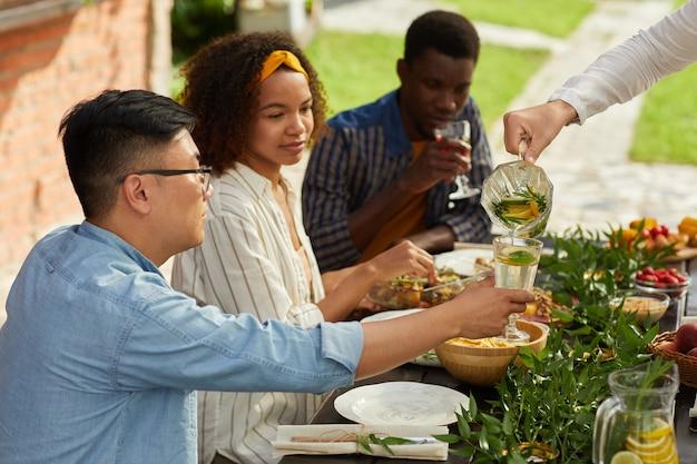 Grupo multiétnico de jovens servindo bebidas enquanto jantam com amigos e família ao ar livre na festa de verão
