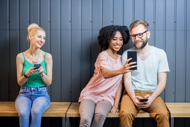Grupo multiétnico de jovens vestidos com camisetas coloridas conversando com gadgets sentados em uma fileira dentro de casa no fundo da parede