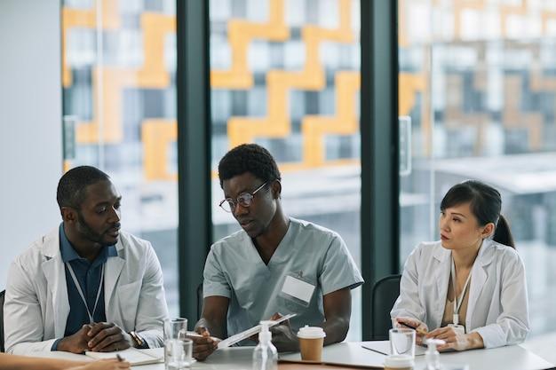 Grupo multiétnico de médicos discutindo o caso enquanto está sentado à mesa de reunião durante o conselho médico, copie o espaço