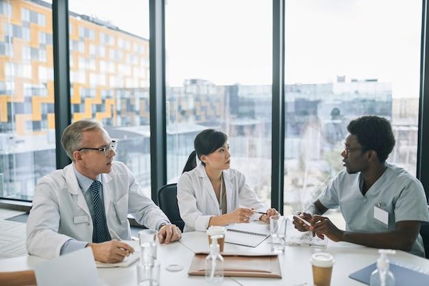 Grupo multiétnico de médicos discutindo o caso enquanto está sentado à mesa de reunião durante uma conferência médica, copie o espaço